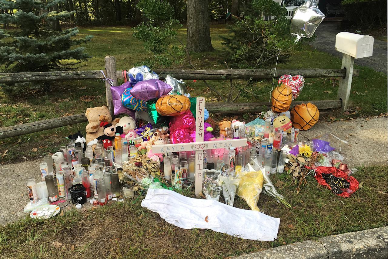 FILE - In this Sept. 27, 2016 file photo, a memorial to best friends Nisa Mickens and Kayla Cuevas is seen near the spot where their bodies were found in Brentwood, N.Y. Mickens, 15, and Cuevas, 16, both students at Brentwood High School, were beaten and hacked to death by a carload of gang members who spotted them walking down the street. Investigators said Cuevas had been feuding verbally with gang members. President Donald Trump is scheduled travel to New York on Friday, July 28, to meet with law enforcement on Long Island and discuss the MS-13 street gang. (AP Photo/Claudia Torrens, File)