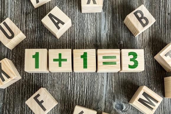 Small wooden blocks on a table showing the formula one plus one equals three.