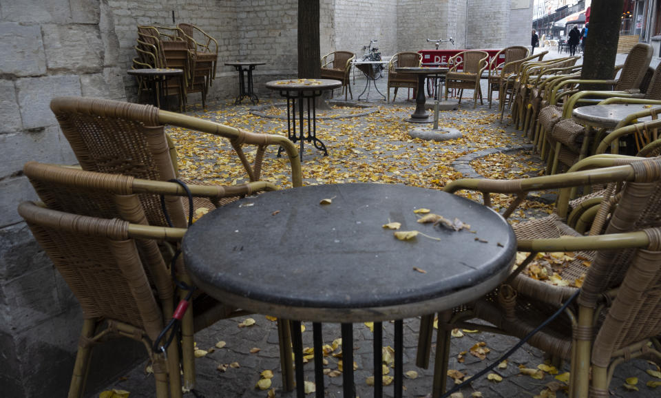 Terrace chairs and tables are chained together in the historic center of Antwerp, Belgium, Sunday, Oct. 18, 2020. Faced with a resurgence of coronavirus cases, the Belgian government on Friday announced new restrictions to try to hold the disease in check, including a night-time curfew and the closure of cafes, bars and restaurants for a month. The measures will take effect on Monday, Oct. 19, 2020. (AP Photo/Virginia Mayo)