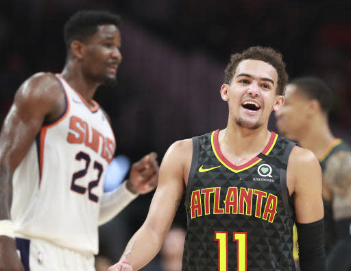 Atlanta Hawks guard Trae Young is all smiles during the final minutes of a 123-110 victory over Deandre Ayton and the Phoenix Suns in an NBA basketball game on Tuesday, Jan. 14, 2020, in Atlanta. (Curtis Compton/Atlanta Journal-Constitution via AP)