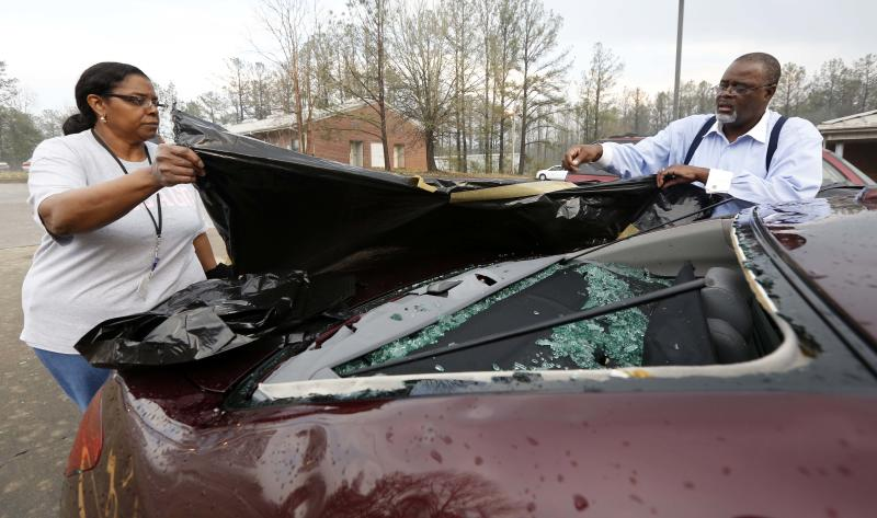 Andrew Stamps and his wife Valorie cover their shattered rear window of her 2009 Toyota Avalon in Pearl, Miss., Monday, March 18, 2013, following a hailstorm that hit communities throughout central Mississippi. The National Weather Service in Jackson says there were a few super cells in central Mississippi and reports of hail up to baseball size in Clinton, golf ball and tennis ball sized in Pearl and Brandon and quarter sized in downtown Jackson, Miss. The Mississippi Emergency Management Agency says severe weather has caused damage in at least 10 counties as the storms moved through parts of the state. (AP Photo/Rogelio V. Solis)