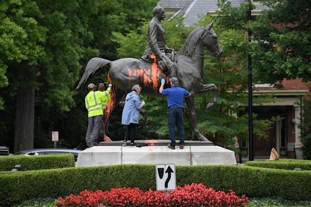 <p>Municipal workers attempt to remove paint from a monument dedicated to Confederate soldier John B. Castleman that was vandalized late Saturday night in Louisville, Ky., Aug.14, 2017. (Photo: Bryan Woolston/Reuters) </p>