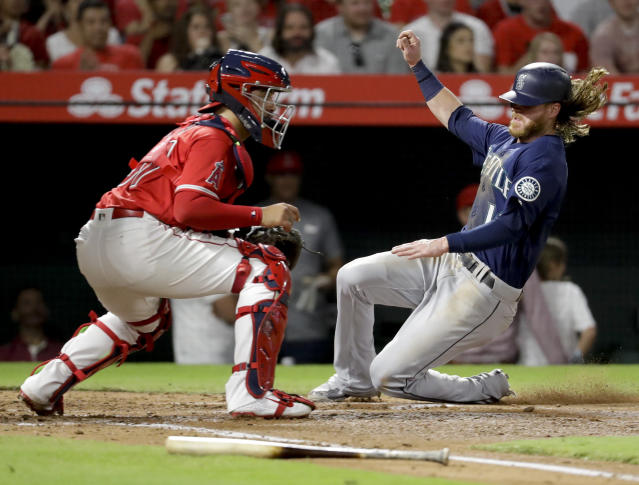 Seattle Mariners' Ben Gamel scores past Los Angeles Angels third baseman Jefry Marte on a sacrifice fly by Dee Gordon during the second inning of a baseball game in Anaheim, Calif., Thursday, Sept. 13, 2018. (AP Photo/Chris Carlson)