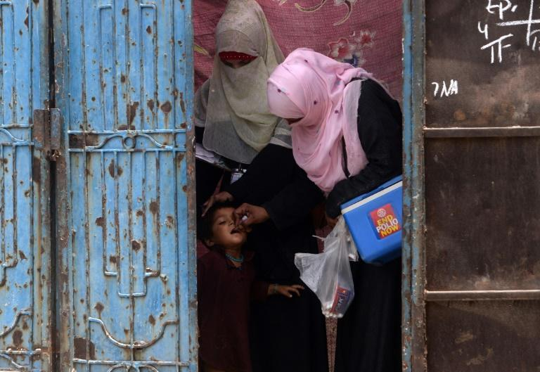 A Pakistani health worker administers polio vaccine to an Afghan refugee in Lahore