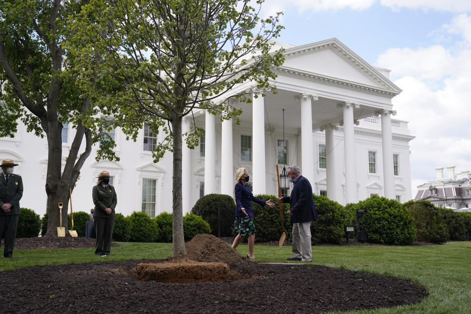 Superintendent of the White House Grounds Dale Haney hands first lady Jill Biden a shovel as she participates in an Arbor Day tree planting ceremony at the White House, Friday, April 30, 2021, in Washington. (AP Photo/Evan Vucci)
