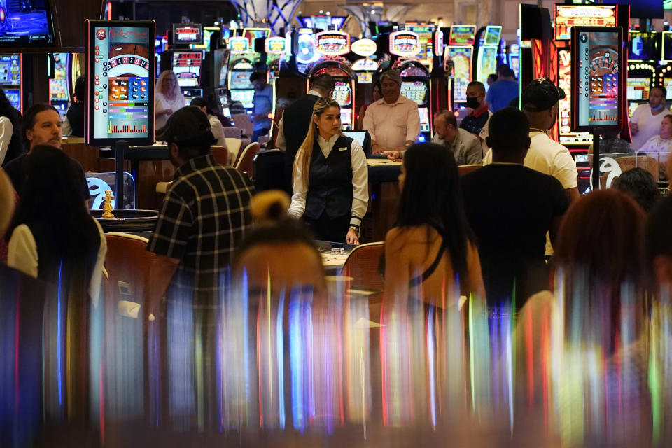In this June 24, 2021, photo, crowds walk through the casino during the opening night of Resorts World Las Vegas in Las Vegas. Las Vegas fully reopened and lifted restrictions on most businesses June 1, though many casino-resorts had already returned to 100% capacity before that with approval from state regulators. Visitor numbers, while not at their pre-pandemic highs, have grown by double digits four months in a row. But this progress is threatened as Nevada this week saw the highest rate of new COVID-19 cases in the country. (AP Photo/John Locher)
