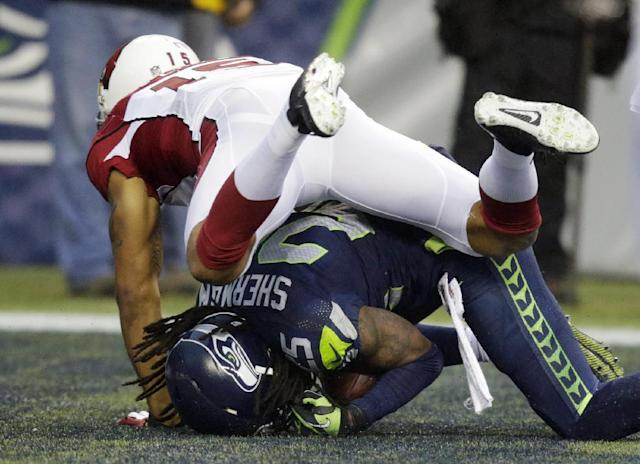 Seattle Seahawks cornerback Richard Sherman, bottom, comes down with an interception of a ball intended for Arizona Cardinals wide receiver Michael Floyd, top, in the second half of an NFL football game, Sunday, Dec. 22, 2013, in Seattle. (AP Photo/Stephen Brashear)