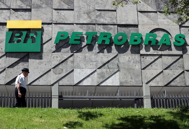 FILE PHOTO: A man walks in front of the headquarters of Petroleo Brasileiro S.A. (Petrobas) in Rio de Janeiro