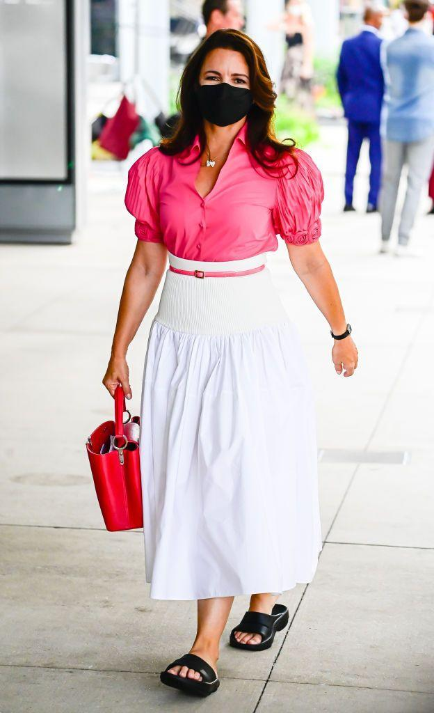 """<p>Another Charlotte York outfit spotted on set is this fuchsia pink puff sleeved shirt, paired with a high-waist white Alexander McQueen cotton skirt (which, surprisingly, is not yet sold out online). She is carrying a Louis Vuitton bag and later changed into some Stuart Weitzman pink pumps for shooting, according @justlikethatcloset.</p><p><a class=""""link rapid-noclick-resp"""" href=""""https://www.selfridges.com/GB/en/cat/alexander-mcqueen-hybrid-high-waist-cotton-and-stretch-woven-midi-skirt_R03762126/"""" rel=""""nofollow noopener"""" target=""""_blank"""" data-ylk=""""slk:SHOP NOW"""">SHOP NOW</a> Alexander McQueen Hybrid high-waist cotton and stretch-woven midi skirt, £1270</p>"""