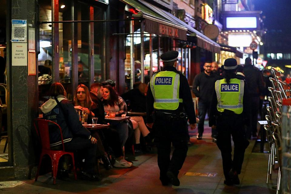 Police officers walk past bars in Soho (Reuters)