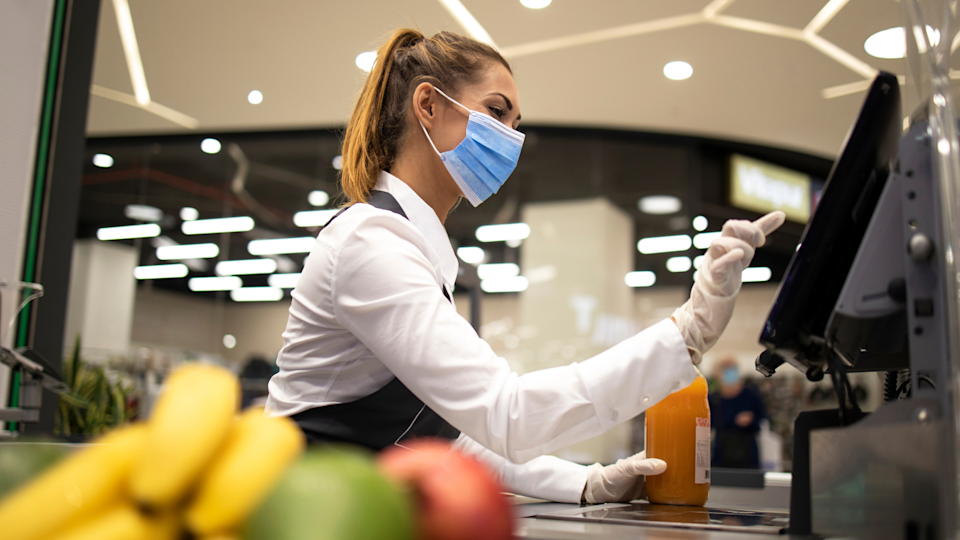 A supermarket worker using a checkout while wearing a mask.