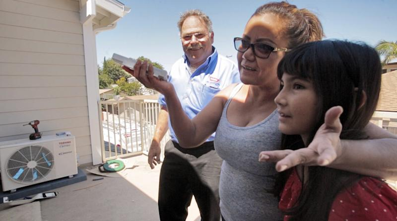 Elvira and her daughter stand on their patio with David Kahn of Kahn Air while they learn about their new Carrier ductless home comfort system. Elvira and her family received one of the 500 systems Carrier donated to Habitat for Humanity.