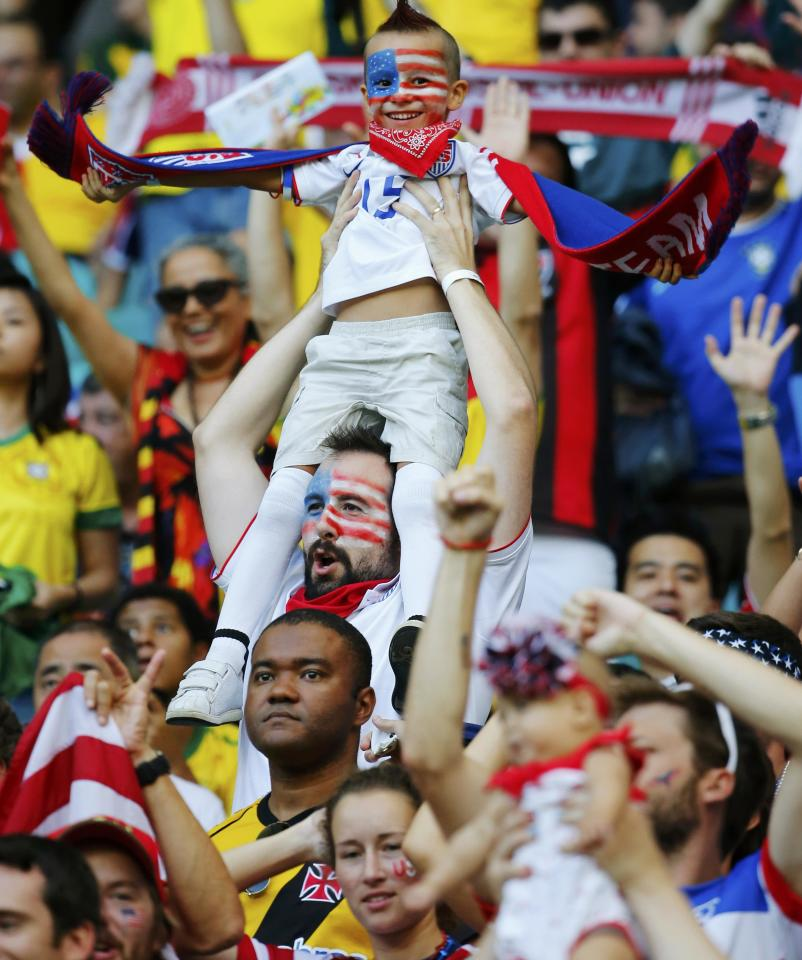A young fan of the U.S. is held above the crowd amid the stands before their 2014 World Cup round of 16 game against Belgium at the Fonte Nova arena in Salvador July 1, 2014. REUTERS/Yves Herman (BRAZIL - Tags: SOCCER SPORT WORLD CUP)