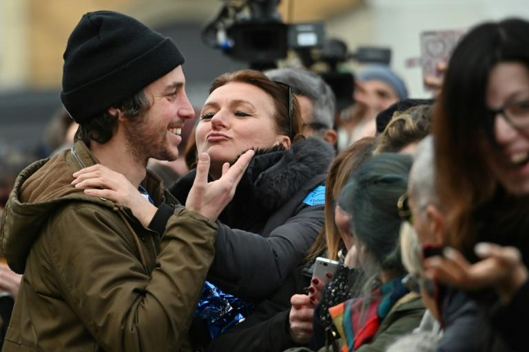 A woman kisses Mattia Santori , one of the founders of the anti-fascist 'Sardine Movement' during a rally this week in Bologna, the capital of Emilia Romagna (AFP Photo/ANDREAS SOLARO)