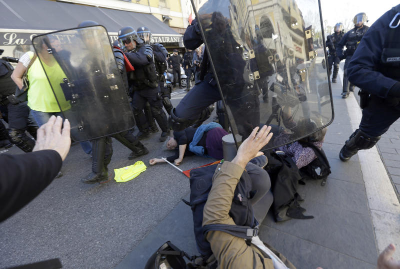 "FILE - In this Saturday, March 23, 2019 file picture, anti-globalization activist Genevieve Legay, 73, center, lies unconscious after collapsing on the ground during a protest in Nice, southeastern France, as part of the 19th round of the yellow vests movement. Genevieve Legay was waving a rainbow flag marked ""Peace"" and a yellow vest when riot police carrying shields suddenly pushed toward the group of a few dozen protesters Saturday. (AP Photo/Claude Paris, File)"