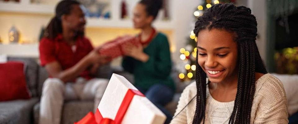 African young smiling girl opening box with Christmas gift