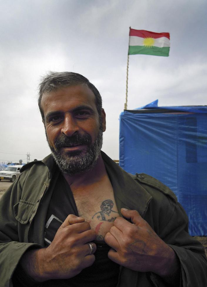 In this Friday, Feb. 15, 2013 photo, Syrian Kurdish refugee Abdel Khader Taha, 37, shows off his tatto of Massoud Barzani, the president of Iraqi Kurdistan, with a flag of Iraqi Kurdistan in the background, in the Dumiz refugee camp in northern Iraq. Syrian Kurds who fled their country's civil war have mixed feelings about a future without Bashar Assad: They hope to win autonomy if the regime falls, but fear chaos and the rise of Islamists could instead make their lives worse. (AP Photo/Karin Laub)