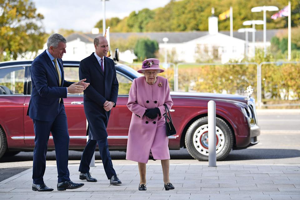 Britain's Queen Elizabeth II (R) and Britain's Prince William, Duke of Cambridge, (C) speak with Dstl Chief Executive Gary Aitkenhead (L) as they head back to the Energetics Analysis Centre during their visit to the Defence Science and Technology Laboratory (Dstl) at Porton Down science park near Salisbury, southern England, on October 15, 2020.