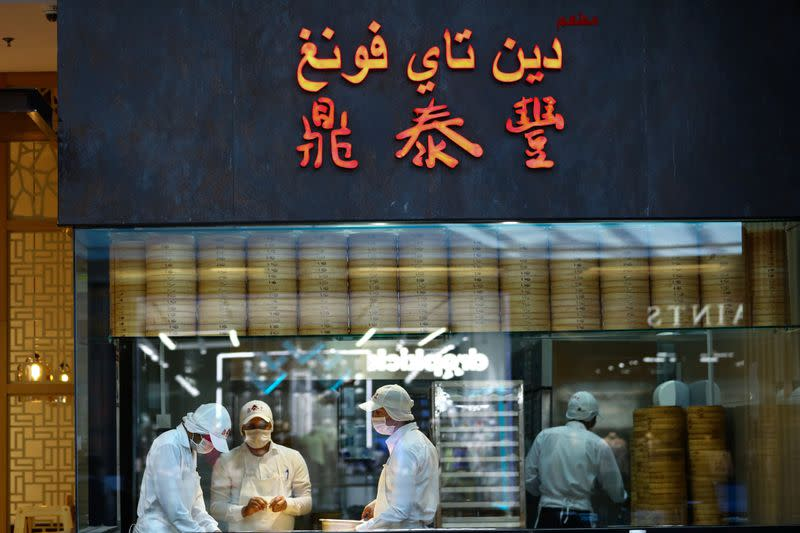 Workers wearing protective face masks prepare food at a restaurant during the reopening of malls, following the outbreak of the coronavirus disease (COVID-19), at Mall of the Emirates in Dubai