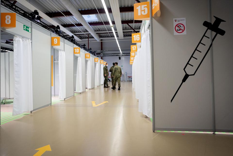 Soldiers of the German Armed Forces stand in a corridor at the newly opened vaccination centre in the area of the Terminal C in the former Berlin Tegel Airport, where inoculation with the OxfordAstraZeneca Covid-19 vaccine starts, in Berlin, on February 10, 2021. - Mainly nursing staff and medical personnel will be vaccinated against the coronavirus here. (Photo by Kay Nietfeld / POOL / AFP) (Photo by KAY NIETFELD/POOL/AFP via Getty Images)