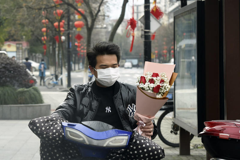 A man wearing a face mask carries a Valentine's Day bouquet as he rides a scooter in Hangzhou in eastern China's Zhejiang Province, Friday, Feb. 14, 2020. China on Friday reported another sharp rise in the number of people infected with a new virus, as the death toll neared 1,400. (Chinatopix via AP)