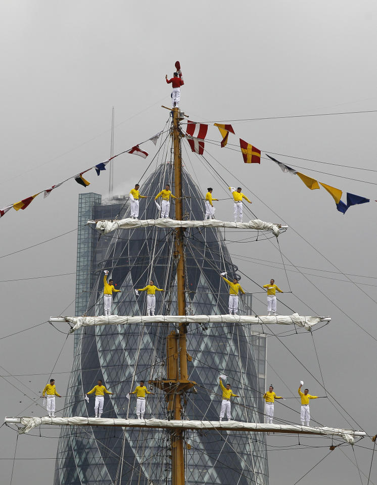 Cadets are seen on the masts sing the ship's anthem as the Colombian Navy's training ship Arc Gloria passes the Swiss RE building - better known as The Gherkin - as cit sails towards Tower Bridge on the River Thames in London, Friday, Aug. 26, 2011. One of the biggest tall ships in the world, which is still in service, the ship is on a three day visit to London. It is almost 20 years since the Colombian Navy's ship Gloria last sailed into London, this time on a goodwill tour of the world, received over 7,000 visitors during its time in the city.(AP Photo/Kirsty Wigglesworth)
