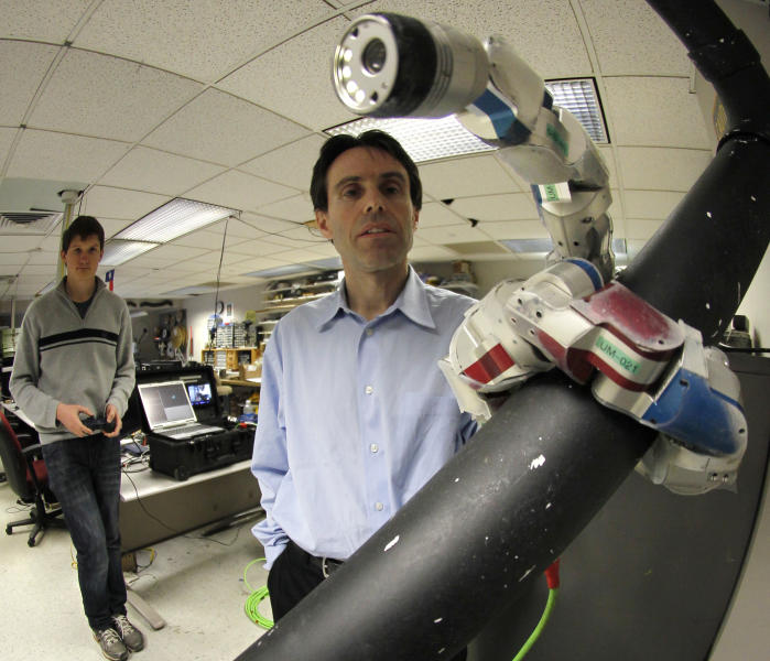 In this April 18, 2012, photo, Carnegie Mellon University professor Howie Choset, right, stands beside a robot as staff researcher Florinan Enner uses a controller to demonstrate how it climbs up a tubular armature at their lab on campus in Pittsburgh. Scientists and doctors are using the creeping metallic tools to perform surgery on hearts, prostate cancer and other diseased organs. (AP Photo/Keith Srakocic)