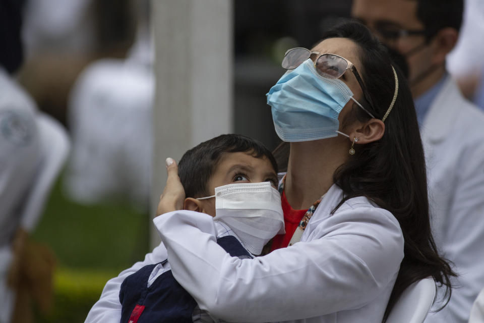 A health worker at the San Juan de Dios hospital holds a child during a minute of silence in memory of her colleagues who have fallen victim to COVID-19 in Guatemala City, Friday, Oct. 9, 2020. (AP Photo/Moises Castillo)