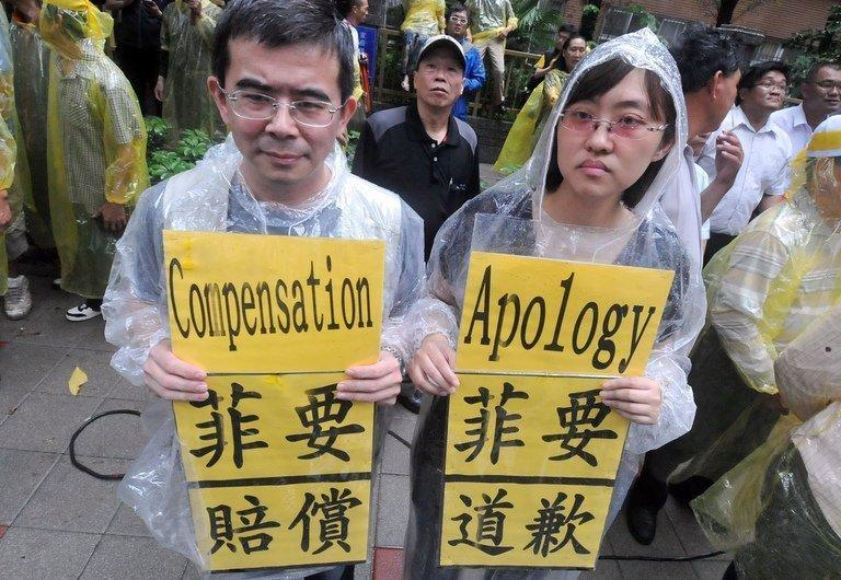 People hold protest signs outside the Philippine de facto embassy in Taipei, on May 13, 2013