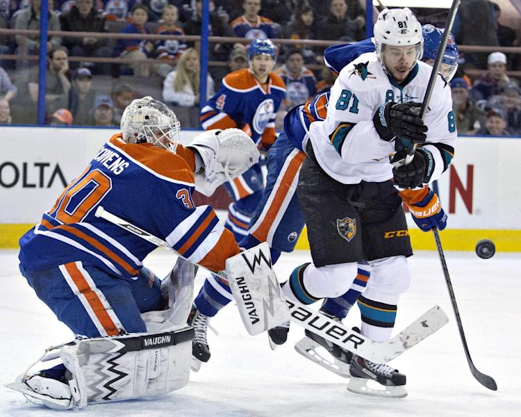 San Jose Sharks Tyler Kennedy (81) and Edmonton Oilers Justin Schultz battle for the rebound as goalie Ben Scrivens, left, makes the save during the first period of an NHL hockey game in Edmonton, Alberta, on Wednesday, Jan. 29, 2014. (AP Photo/The Canadian Press, Jason Franson)