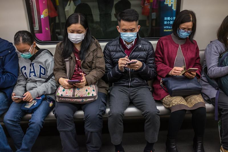 "People wear masks on a train on the first day of the Lunar New Year of the Rat in Hong Kong on January 25, 2020, as a preventative measure following a coronavirus outbreak which began in the Chinese city of Wuhan. - Hong Kong on January 25 declared a mystery virus outbreak as an ""emergency"" -- the city's highest warning tier -- as authorities ramped up measures aimed at reducing the risk of further infections spreading. (Photo by DALE DE LA REY / AFP) (Photo by DALE DE LA REY/AFP via Getty Images)"
