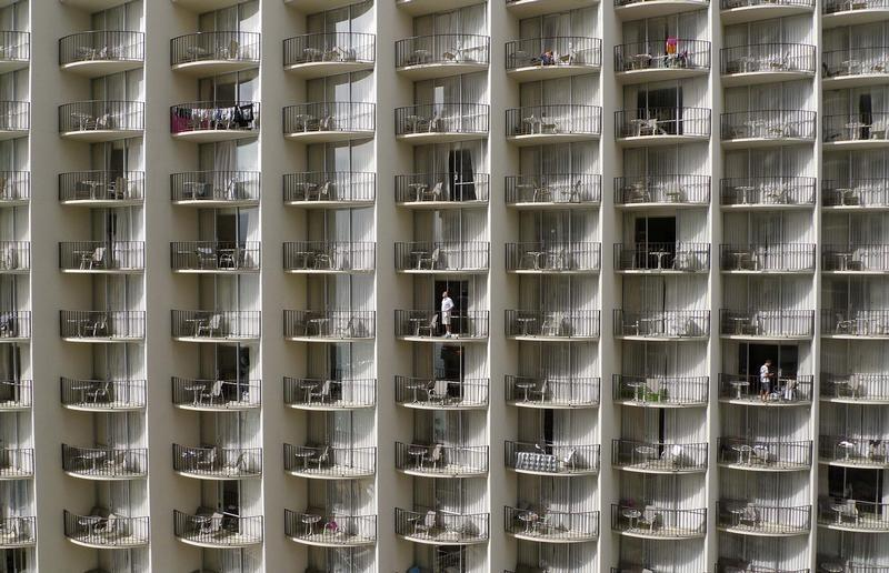 Men stand at the balconies of their hotel rooms on Waikiki Beach in Honolulu