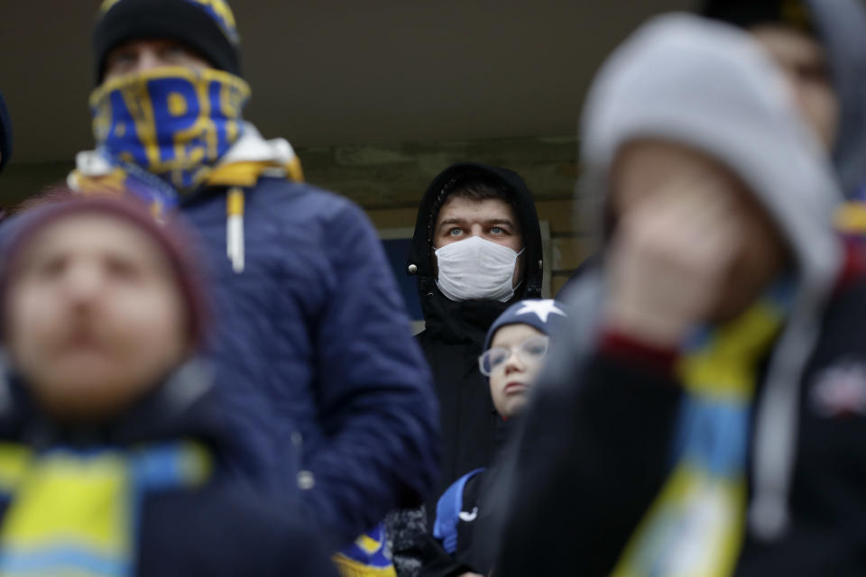 In this photo taken on Thursday, March 19, 2020, football fans of FC Bate, one of them wearing a face mask, watch the Belarus Championship soccer match between Energetik-BGU and Bate in Minsk, Belarus. Longtime Belarus President Alexander Lukashenko is proudly keeping soccer and hockey arenas open even though most sports around the world have shut down because of the coronavirus pandemic. The new coronavirus causes mild or moderate symptoms for most people, but for some, especially older adults and people with existing health problems, it can cause more severe illness or death. (AP Photo/Sergei Grits)