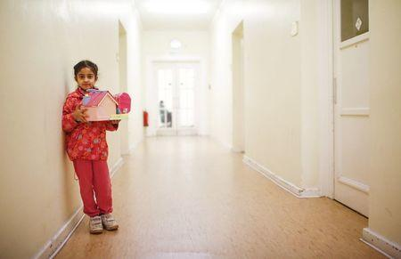 A girl holds a toy at a refugee shelter run by German charity organisation Arbeiter Samariter Bund ASB in Berlin, Germany, December 12, 2015. REUTERS/Hannibal Hanschke