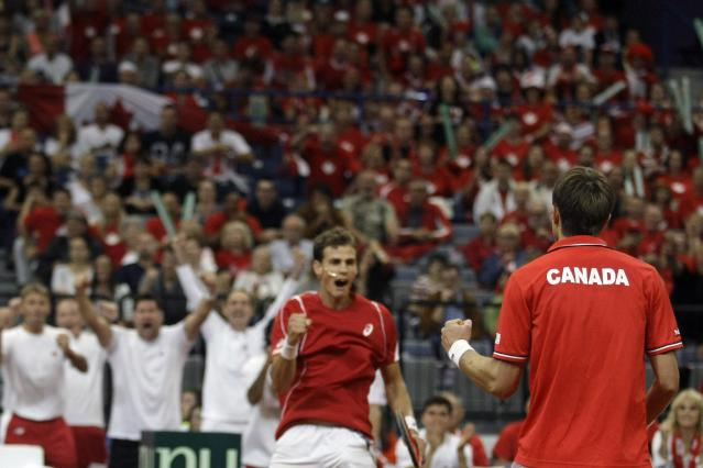 Canada's Daniel Nestor, right, and Vasek Pospisil celebrate winning a set from Serbia's Nenad Zimonjic and Ilija Bozoljac during their Davis Cup semifinal tennis double match in Belgrade, Serbia, Saturday, Sept. 14, 2013. (AP Photo/ Marko Drobnjakovic)