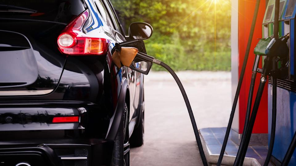Pumping gasoline fuel in car at gas station,travel,transportation and holiday concept.
