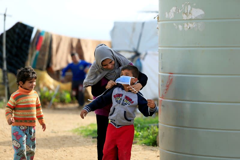 FILE PHOTO: A Syrian refugee woman puts a face mask on a boy as a precaution against the spread of coronavirus, in al-Wazzani area in southern Lebanon