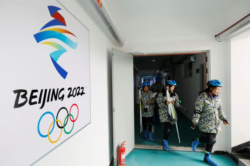 Students leaving an equipment room are seen next to a Beijing 2022 emblem at a middle school in Zhangjiakou