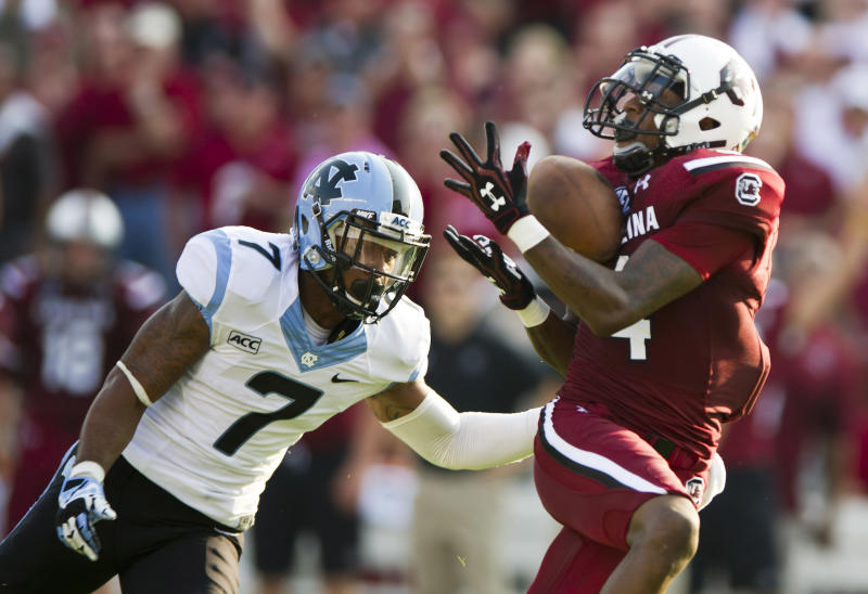 South Carolina wide receiver Shaq Roland (4) catches a touchdown pass while being defended by North Carolina cornerback Tim Scott (7) during the first half of an NCAA college football game, Thursday, Aug. 29, 2013, in Columbia, S.C. (AP Photo/Stephen Morton)