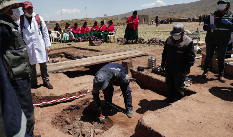 Workers extract pre-Hispanic vessels at the Kalasasaya temple in the ancient city of Tiwanaku, Bolivia, Wednesday, Sept. 18, 2019. Bolivian archaeologists will present the findings of a recent discovery of ancient vessels unearthed in a dig on the site once home to one of the most significant pre-Hispanic empires, the Tiwanacota. (AP Photo/Juan Karita)
