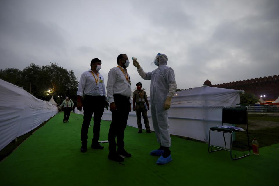 A man dressed in protective suit checks the body temperature of attendees before the start of the Independence Day ceremony on the ramparts of the landmark Red fort monument in New Delhi, India, Saturday, Aug. 15, 2020. India's coronavirus death toll overtook Britain's to become the fourth-highest in the world with another single-day record increase in cases Friday. (AP Photo/Manish Swarup)