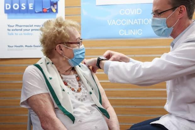 Corrie Hudson, 88, was the first New Brunswicker over 85 to receive COVID-19 vaccine from a pharmacist on Wednesday in Fredericton. Pharmacist Ryan Quinn administered the shot.
