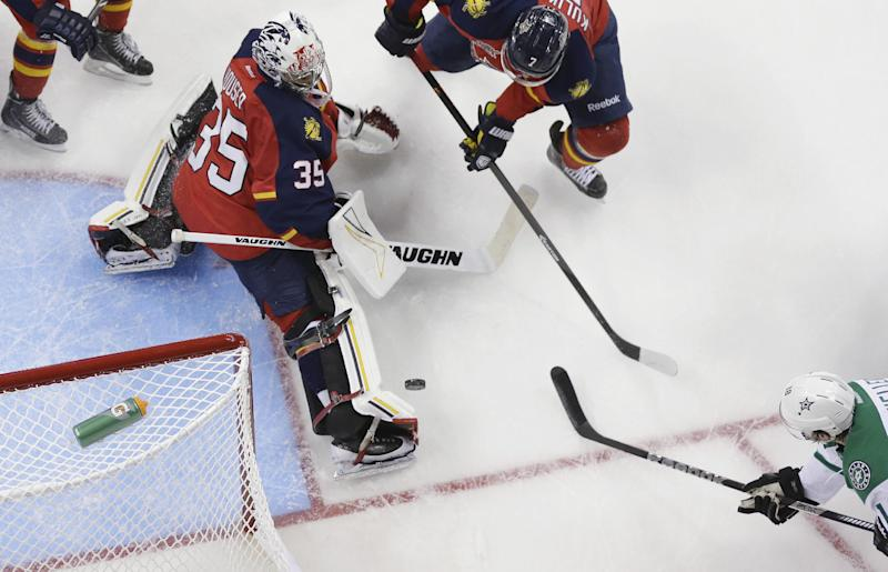 Florida Panthers' Michael Houser (35) blocks a shot on goal by Dallas Stars' Chris Mueller, right, during the first period of a preseason NHL hockey game, Friday, Sept. 20, 2013, in San Antonio. Florida Panthers' Dmitry Kulikov (7) assists on the play. (AP Photo/Eric Gay)