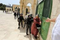 Israeli border policeman shouts on a Palestinian woman at the compound that houses Al-Aqsa Mosque in Jerusalem's Old City