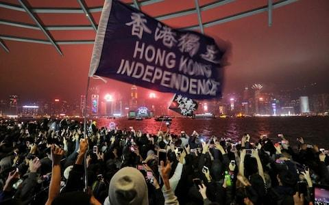 <span>Protesters chant as fireworks explode in Hong Kong along the waterfront on new year's eve in Tsim Sha Tsui</span> <span>Credit: Rex </span>