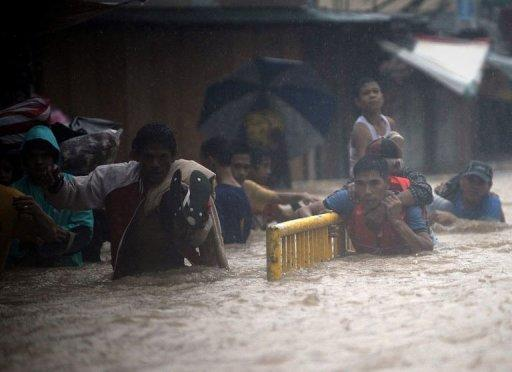 Residents wade through a flooded street to reach safety in a village near Manila