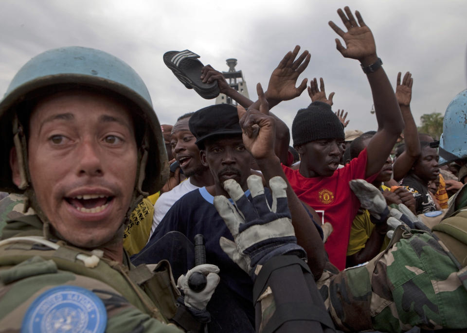 <p>United Nations soldiers from Uruguay hold the crowd back during a food distribution in Port-au-Prince, Monday, Jan. 25, 2010. (Photo: Ramon Espinosa/AP) </p>