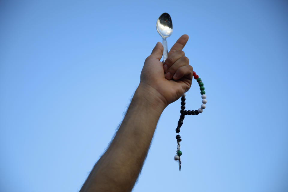 A protester holds a spoon, which has become a symbol celebrating the six Palestinian prisoners who recently tunneled out of Gilboa Prison, in Umm el-Fahm, Israel, Friday, Sept. 10, 2021. (AP Photo/Ariel Schalit)
