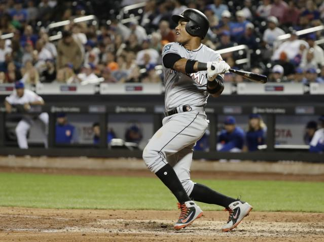 Miami Marlins' Starlin Castro (13) follows through on a RBI single during the ninth inning of a baseball game against the New York Mets Wednesday, May 23, 2018, in New York. (AP Photo/Frank Franklin II)