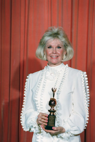 FILE - In this Jan. 28, 1989 file photo, actress and animal rights activist Doris Day poses with the Cecil B. DeMille Award she was presented with at the annual Golden Globe Awards ceremony in Los Angeles, Calif. Day is celebrating a landmark birthday with an auction to benefit her favorite cause: animals. A spokesman for Day said Tuesday, March 11, 2014, the nonprofit Doris Day Animal Foundation will mark her 90th birthday in April with a bash in Carmel, Calif. (AP Photo, file)